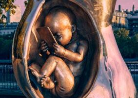 Uma escultura de um feto no útero com um smartphone